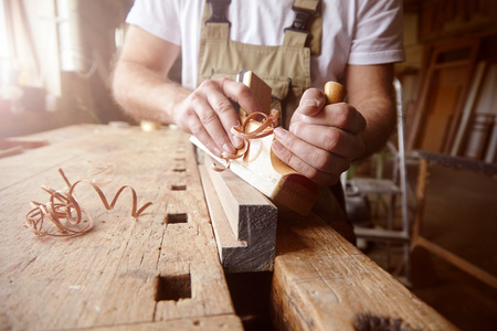 Mid section of male carpenter using wood plane at workbench