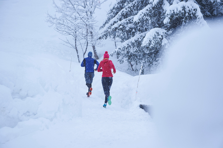 Rear view of male and female runners running on track in deep snow, Gstaad, Switzerland