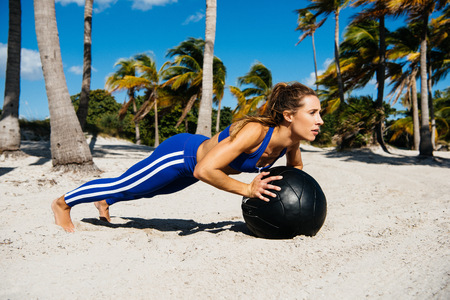 Young woman training, doing push ups on exercise ball at beach LANG_EVOIMAGES