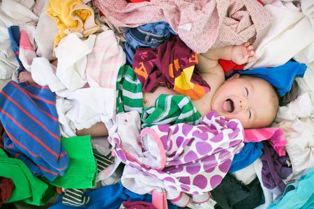 Overhead view of yawning baby girl lying amongst laundry