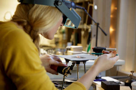 Female jewellery maker using miniature blowtorch in design studio LANG_EVOIMAGES