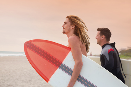 finding out: Male lifeguard and surfer looking out to sea from beach