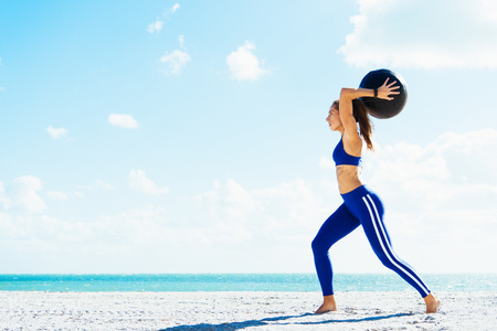 Young woman training, preparing to throw exercise ball on beach LANG_EVOIMAGES
