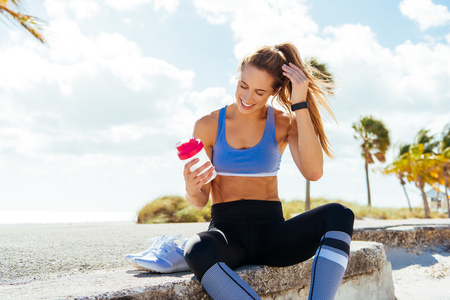 Young female runner sitting with takeaway drink on beach wall LANG_EVOIMAGES