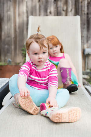Two young sisters sitting on lounge chair in garden