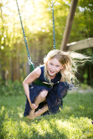 flyaway: Portrait of girl crouching while swinging on garden swing