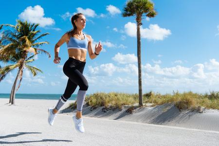 Young female runner running at beach
