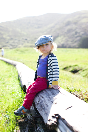Portrait of male toddler in flat cap sitting on log