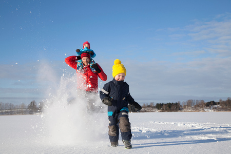 Father and two sons fooling around, running through snow covered landscape LANG_EVOIMAGES