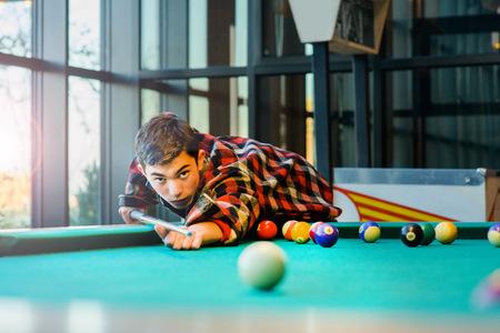 Teenage boy playing pool billiards