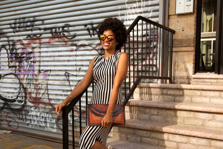 bajando escaleras: Young female fashion blogger with afro hair on urban stairs, New York, USA