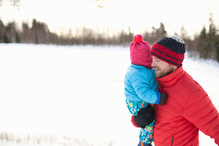 Father carrying young son in snow covered landscape LANG_EVOIMAGES