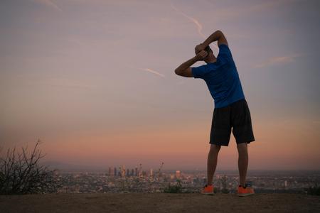 Rear view of jogger stretching at dusk, Runyon Canyon, Los Angeles, California, USA LANG_EVOIMAGES