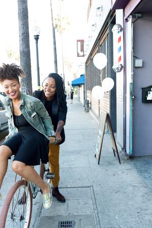 barbershop: Female barber partners having fun on bicycle outside barber shop