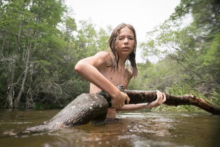 Teenage boy in lake holding tree branch LANG_EVOIMAGES