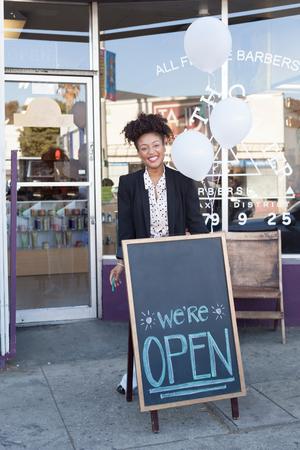 barbershop: Portrait of happy female barber outside barber shop front