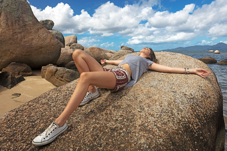 Teenage girl lying on rock sunbathing