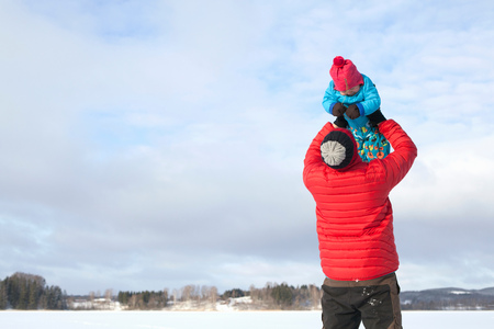 Father lifting young son in air, in snow covered landscape
