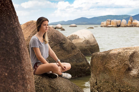 Teenage girl sitting cross legged on rocks by sea looking away