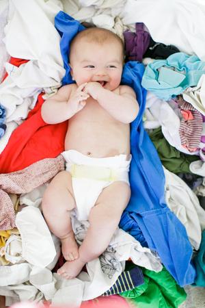 6 12 months: Overhead portrait of baby girl lying amongst laundry