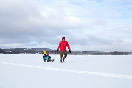 Father pulling sons along on sledge in snow covered landscape
