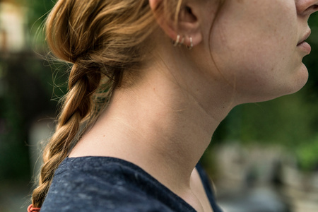 Side view of woman with plaited red hair