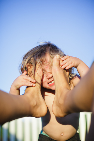 Male toddler with face against mothers bare feet LANG_EVOIMAGES