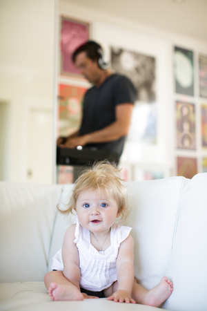 6 12 months: Portrait of baby girl sitting on sofa LANG_EVOIMAGES