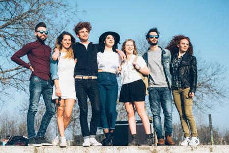 milánó: Portrait of group of friends,standing on ledge