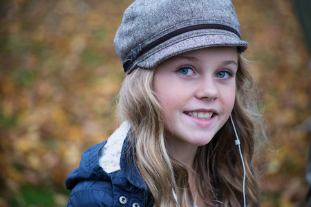 wired: Portrait of blond girl in baker boy cap listening to earphone music