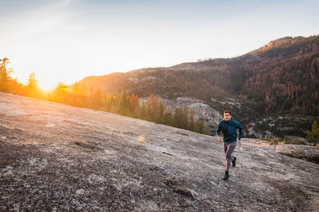 anorak: Man running on rock surface at sunset,Yosemite National Park,California,USA LANG_EVOIMAGES