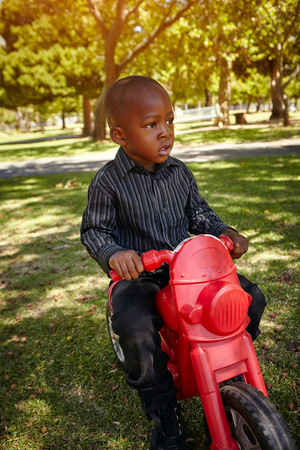 Boy riding motorcycle in park