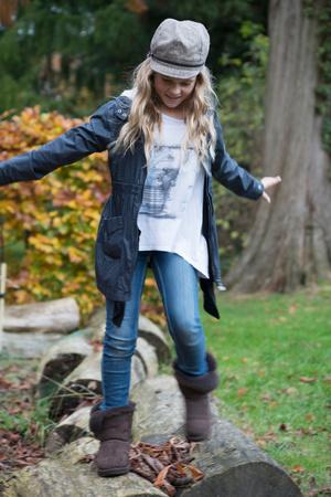 Girl stepping over logs in park
