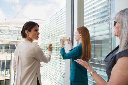 conferring: Businesswomen brainstorming ideas on glass window