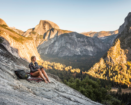 Woman on rock looking out at valley forest,Yosemite National Park,California,USA