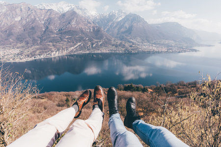 personal perspective: Legs of couple over mountain lakeside,Monte San Primo,Italy