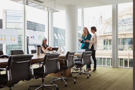 conferring: Businesswomen preparing presentation in meeting room LANG_EVOIMAGES