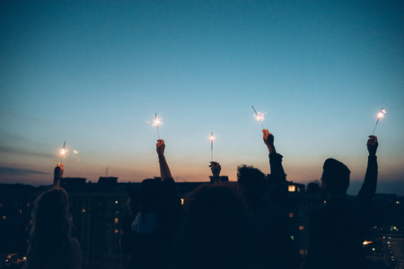 Group of friends enjoying roof party,holding lit sparklers in air,rear view