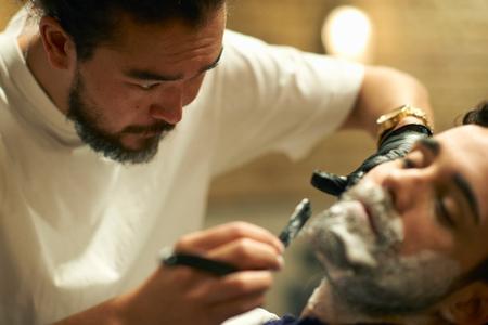 barbershop: Hairdresser in barbershop giving customer wet shave