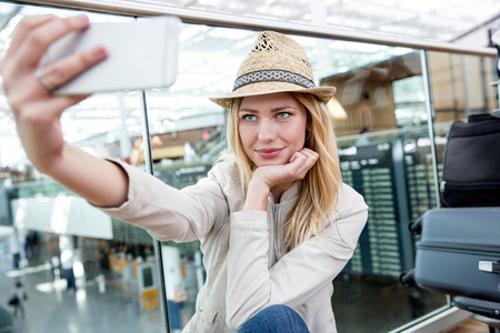 Young woman taking smartphone selfie in airport terminal