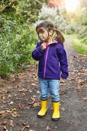 Portrait of young girl on rural pathway,looking through magnifying glass LANG_EVOIMAGES