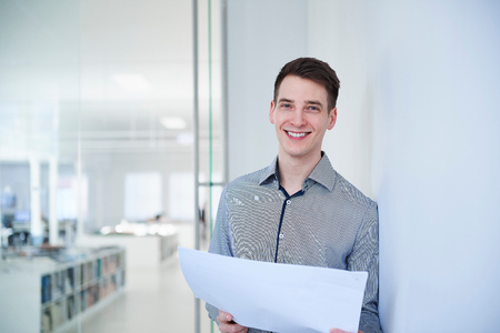 Portrait of architect in office holding blueprints looking at camera smiling