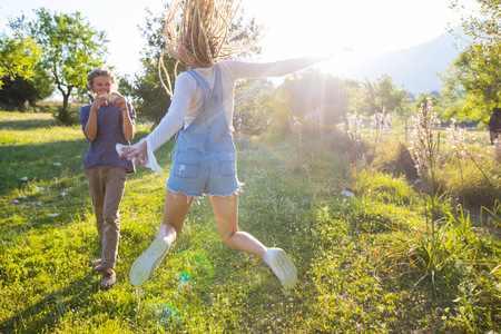 flyaway: Fun young woman jumping in field being photographed by boyfriend,Majorca,Spain