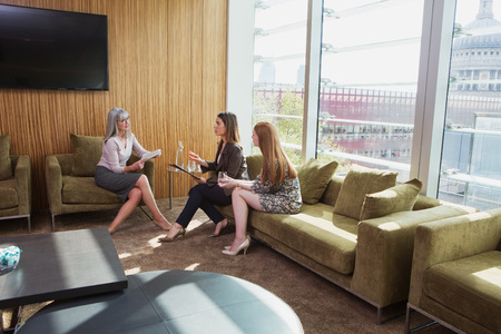 conferring: Businesswomen meeting on office sofa,London,UK