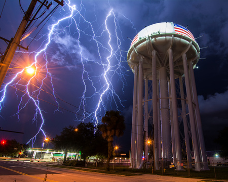 forked: Spectacular lightning bolt with simultaneous branches strikes Cocoa,Florida,amid power lines near the citys water tower