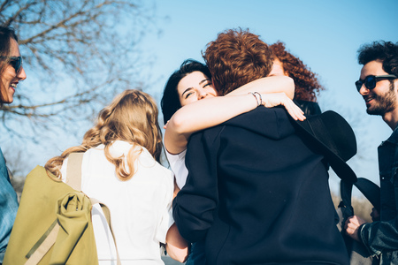 Group of friends hugging,outdoors LANG_EVOIMAGES