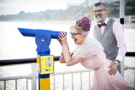 1950s vintage style couple looking through coin operated binoculars on pier LANG_EVOIMAGES