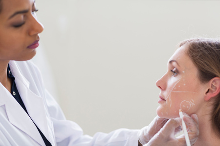 self conceit: Cosmetic surgeon marking patients face for surgery LANG_EVOIMAGES