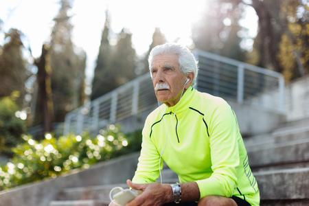 Portrait of senior man holding smartphone looking away