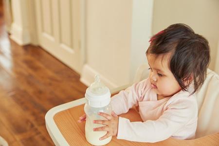 Baby girl holding baby milk bottle on high chair